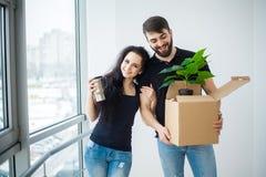 Het glimlachende paar pakt dozen in nieuw huis uit Stock Foto