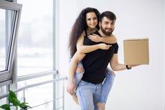 Het glimlachende paar pakt dozen in nieuw huis uit Stock Fotografie