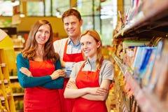 Het glimlachende personeel van het verkoopteam in supermarkt Stock Foto's
