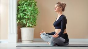 Het glimlachende prettige mooie meisje die van meditatie in lotusbloem genieten stelt het ontspannen bij studio volledig schot stock footage