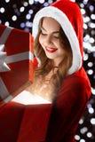 Het glimlachende Sneeuwmeisje in rood kostuum opent een gift voor Nieuwjaar 2018.2019 Stock Afbeeldingen