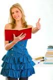Het glimlachende tienermeisje met boek het tonen beduimelt omhoog Royalty-vrije Stock Afbeelding