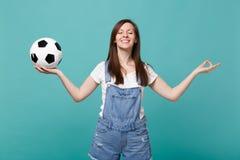 Het glimlachende van de de ventilatorsteun van de vrouwenvoetbal favoriete team met de greep van de voetbalbal dient yogagebaar i stock foto
