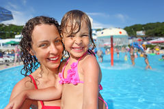 Het glimlachende vrouw en meisje baden in pool royalty-vrije stock afbeelding