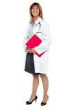 Het glimlachende vrouwelijke klembord van de artsenholding stock afbeeldingen