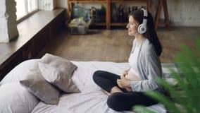 Het glimlachende zwangere meisje luistert aan muziek in hoofdtelefoons, streelt binnen haar buik en ontspant zitting op tweeperso stock videobeelden
