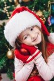 Het glimlachmeisje in rode hoed houdt een boomdecoratie Stock Foto