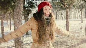 Het glimlachmeisje werpt sneeuw stock footage