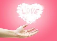 Het gloeien de vorm van het Wolkenhart drijft op open vrouwenhand op speld Stock Foto