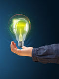 Het gloeien lightbulb in de hand van een vrouw Royalty-vrije Stock Afbeelding