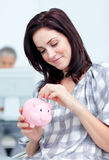 Het gloeiende geld van de onderneemsterbesparing in een piggy-bank stock afbeelding