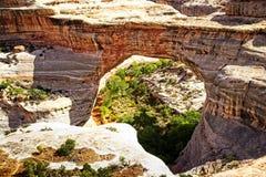 Het gluren door een massieve natuurlijke brug Stock Foto