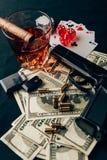 Het gokken concept met kanon, whisky en geld op casinolijst met kaarten royalty-vrije stock fotografie