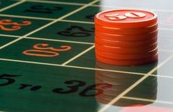 Het gokken van Spaanders op een roulettelijst Stock Foto's