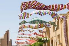Het golven in hemelstof Multicolored zijde textielproducten die tegen de blauwe hemel fladderen Slinger van helder in de wind wor stock foto