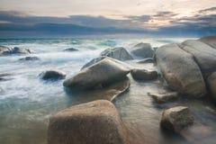 Het golven over steen in een strand Stock Foto's