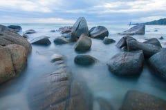 Het golven over steen in een strand Stock Afbeelding