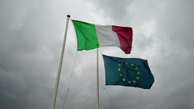 Het golven stoffentextuur van de vlag van Italië en unie Europa op hemel met bewolkte hemel, concept zaken, stock footage