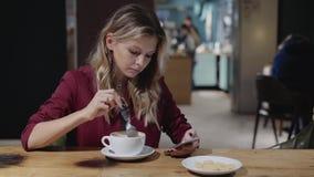 Het golvende Web die van de blonde Kaukasische vrouw in een alleen koffie surfen stock footage