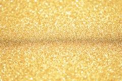 Het goud en schittert achtergrond met smalle nadruk Stofgoud Stock Foto