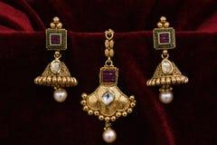 Het goud plateerde Juwelen - de close-up macrobeeld van Ontwerper gouden oorringen op rode achtergrond royalty-vrije stock afbeelding