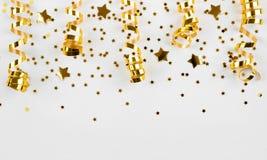 Het goud speelt confettien en gekrulde die linten mee op witte achtergrond worden geïsoleerd Royalty-vrije Stock Afbeeldingen