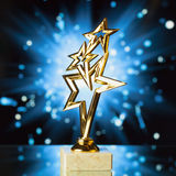 Het goud speelt trofee tegen blauwe glanzende achtergrond mee Royalty-vrije Stock Afbeelding