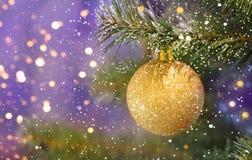 Het gouden bal hangen op de boom op de achtergrond van lichten stock afbeelding