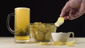 Het gouden bier wordt gegoten langzaam aan het glas, neemt de mens potatoe spaanders en dompelt hen in de saus onder, snacks voor stock videobeelden