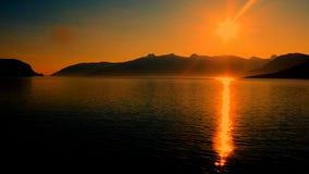 Het gouden flikkeren over de fjord met bergen in de rug stock fotografie