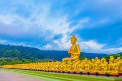 het gouden grote standbeeld van Boedha onder heel wat kleine standbeelden van Boedha Stock Foto's
