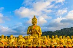 het gouden grote standbeeld van Boedha onder heel wat kleine standbeelden van Boedha Stock Foto
