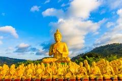 het gouden grote standbeeld van Boedha onder heel wat kleine standbeelden van Boedha Royalty-vrije Stock Afbeelding