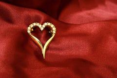 Het gouden hart van juwelen op rode zijde Royalty-vrije Stock Afbeeldingen