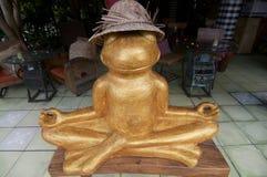Het gouden kikkerstandbeeld in het mediteren stelt royalty-vrije stock foto's