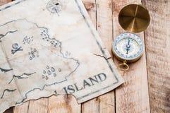 Het gouden kompas met retro en uitstekende kaart van vals eiland met Piraten waardeert borst Royalty-vrije Stock Fotografie