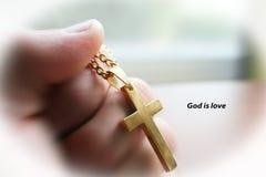 Het gouden Kruis ter beschikking met God is Liefde met Wit Hoog Kader - kwaliteit Stock Foto