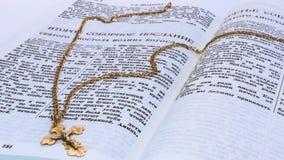 Het gouden kruis van de kruisiging van Christus op heilige scripture van de oude overeenkomst op de pagina met de tekst van de tw royalty-vrije stock afbeelding
