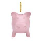 Het gouden muntstuk daalt in een roze spaarvarken Stock Afbeeldingen