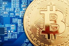 Het gouden muntstuk van bitcoin ligt op de videokaart Stock Foto's