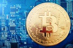 Het gouden muntstuk van bitcoin ligt op de videokaart Stock Foto