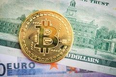 Het gouden muntstuk van bitcoin ligt op dollar en euro Royalty-vrije Stock Foto's