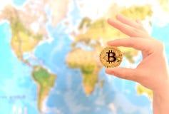 Het gouden muntstuk van de handholding van Bitcoin tegen kaart van wereld Bitcoin stock foto