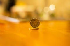 Het gouden muntstuk van het vijftig eurocentenmuntstuk met een waarde van één rand op de oppervlakte van een andere muntstukken Stock Foto