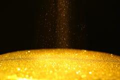 Het gouden poeder met schittert lichten op zwarte achtergrond met exemplaarruimte stock afbeelding