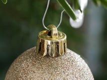 Het gouden Snuisterij hangen neer van een Tak van Kerstboom Ondiep dieptegebied stock afbeeldingen