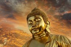 Het gouden standbeeld van Boedha tegen een mooie zonsondergang Royalty-vrije Stock Afbeeldingen