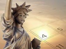 Het gouden Standbeeld van het bronsmetaal van Vrijheid en 4 van Juli op kalenderpagina met vage idyllische aard van de achtergron stock afbeelding