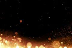 Het gouden stromende effect van gloeddeeltjes bokeh op zwarte achtergrond, vakantie gelukkig nieuw jaar stock fotografie
