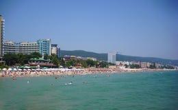 Het gouden Zand neemt, Bulgarije - Juli 13 2012 zijn toevlucht: toeristen die pret op de kust hebben die in de Zwarte Zee zwemmen Stock Foto's
